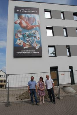 Aileen Seeber, Sekretärin der Geschäftsleitung, präsentiert Herrn Bürgermeister Matthias Reinz, und Geschäftsführer Dr. Manfred Bohn stolz die Außenwerbung am Gebäude, woran sie maßgeblich beteiligt war.